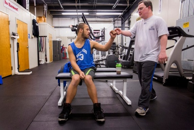 Jon Atkins,19, left, greets his friend Nate Morell of Virginia Beach, right, with a fist bump before their work out at Houze Of Champions gym in Virginia Beach under the direction of personal trainer, Joe Hartfelder Wednesday, Feb. 15, 2017. Atkins was working out just days before his first body building competition in Hampton for The Body Sculpting Open Championships at The American Theatre. Atkins, who has Down Syndrome has worked with Hartfelder for the past year in preparing for the competition. Morell also has Down Syndrome.