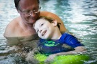Bill Saville helps Jackson during an aqua therapy session led by ​Rebecca Gayle, ​physical therapist at Children's Hospital of The King's Daughters, at William Farm Recreation Center in Virginia Beach, Va., on Monday, May 16, 2017. Stacy Saville enrolled Jackson into the therapy to help continue to strengthen his body following the Spinraza injections. Since starting the injections his mom says his legs and arms more, he is sitting up so much straighter and his grip is so much tighter