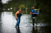 2nd PLACE MULTIPLE: KRISTEN ZEIS, VIRGINIAN-PILOT--Kristen and Jason Atoigue, walk through flood waters after taking a boat to their house to retrieve their flood insurance papers and their sons hamster in Pender County, N.C., on Friday, September 21, 2018. The Atoigue's house is 15 feet above the water and they still have a couple of feet of water in their residence. Hurricane Florence made landfall on Friday, September 14, 2018 and brought over 23 inches of rain to the area. The storm left over 2,400 storms damaged in Pender County with an estimated 25 percent of the homes underwater.