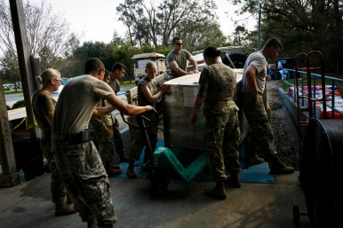 National Guard members unload MRE's and supplies for a distribution center set up by Pastor Jeff Daw at Lighthouse Worship Center in Rocky Point, N.C., on Saturday, September 22, 2018.