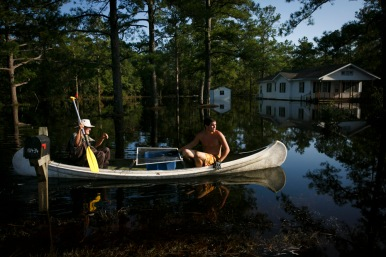 Richard Walton and Austin Smigiel, of Rocky Point, N.C., rescue chickens following flooding of the area after Hurricane Florence on Sunday, September 23, 2018. An overpass across the Northeast Cape Fear River was flooded, leaving residents who didn't make it out in time stranded and relying on the delivery of supplies and food from outside boats.