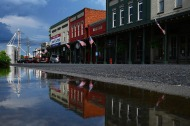 Buildings on Main Street are reflected in a rain puddle on Monday August 06, 2018 in Plains, GA. Born in Plains, GA, President Jimmy Carter stayed in the town following his presidency.
