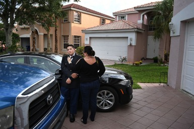Kyle Laman, 15, has his bow tie adjusted by his mother, Marie Laman outside the family's home before Kyle attended a JROTC military ball on Saturday April 21, 2018 in Coral Springs, FL. His parents had to coax him out of the house to attend the event. Kyle was shot in during a deadly mass shooting at Marjory Stoneman Douglas High School on February 14, 2018.