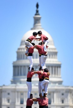 1st PLACE FEATURE: MATT MCCLAIN, WASHINGTON POST--The United States Capitol is seen in the background as Smithsonian Folklife Festival participants form a human tower along the National Mall on Sunday July 08, 2018 in Washington, DC. The cultures of Catalonia and Armenia were highlighted in this year's festival. The human tower tradition is celebrated in Catalonia.