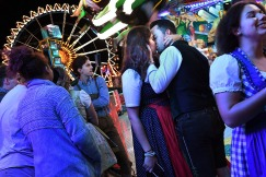 2nd PLACE FEATURE: MATT MCCLAIN, WASHINGTON POST--Marie-Noel Achkar and Max Nelson kiss near a ride at Oktoberfest on Saturday September 22, 2018 in Munich, Germany. The annual event opened Saturday and runs through October 7th.
