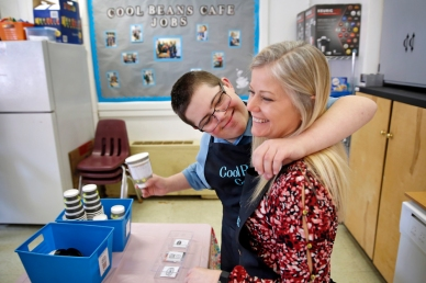 1st PLACE FEATURE: JONATHON GRUENKE, DAILY PRESS--Jake Mann hugs Betsy Ferguson while working at Poquoson Middle School's Cool Beans Cafe Thursday morning. Special needs students run all aspects of the coffee shop which help them get experience with job skills and social interactions outside a typical classroom environment.