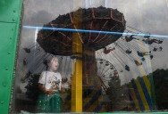 2nd PLACE FEATURE: Matt McClain, Washington Post--Emily Barroso, 3, looks out a window of the Lily's Storyland attraction while people on the Wave Swinger ride are reflected at a carnival that was part of the Celebrate Fairfax festival on Sunday June 10, 2018 in Fairfax, VA.