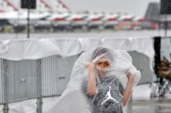 HM Feature Jonathon Gruenke, Daily Press--Jaidon Lee takes cover under a plastic bag in front the parked Thunderbirds as heavy rain begins to fall during Saturday's Air Power over Hampton Roads at Langley Air Force Base Saturday May 19, 2018.