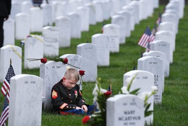 1st PLACE NEWS: MATT MCCLAIN, WASHINGTON POST Christian Jacobs, 7, sits against the headstone of his father, U.S. Marine Corps Sgt. Christopher James Jacobs as he visits in observance of Memorial Day at Arlington National Cemetery on Monday May 28, 2018 in Arlington, VA. Christopher died during a training exercise in 2011.