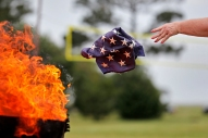 HM NEWS: JONATHON GRUENKE, DAILY PRESS--Margaret Wilkins disposes a piece of an American flag into a fire during a flag retirement ceremony on Fort Monroe Monday May 28, 2018. Hundreds of people, eight different Boy Scout Troops, the National Park Service and veterans gathered to retire close to 400 flags by burning them with dignity and respect.