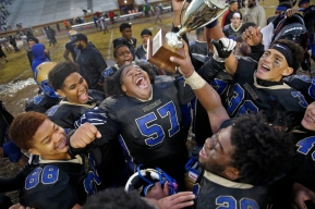 1st Place Sports: Jonathon Gruenke, Daily Press---Phoebus' Ramel Lewis, center, other players celebrate with the trophy after defeating Norcom 7-6 in triple overtime during Saturday afternoon's Class 3 Region A championship game at Darling Stadium November 24, 2018.