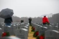 3rd Place Feature: Kristen Zeis, Virginian-Pilot--- Chief Petty Officer Franklin Cheromiah watches over as volunteers and loved ones place over 9,000 live wreaths at grave sites as part of the Horton Wreath Society wreath laying event at Albert G. Horton Jr. Memorial Veterans Cemetery in Suffolk, Va., on Saturday, December 15, 2018. This was the 11th year the society put on the event.