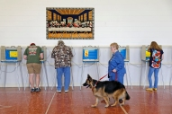 HM News: Jonathon Gruenke, Daily Press---Susie Nelson walks past a painting of the Last Supper with german shepherd, Cali, as voters cast their ballots at Trinity United Methodist Church in Poquoson Tuesday afternoon November 6, 2018.