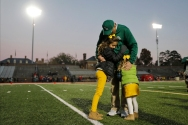 HM Place Sports: Jonathon Gruenke, Daily Press---William and Mary head football coach Jimmye Laycock hugs his granddaughters Grail Johnson, left, and Nolan Johnson after the conclusion of Saturday's game against the University of Richmond at Zable Stadium November 17, 2018. Saturday concluded his 39th and final season as William and Mary's head football coach. Laycock holds the third-longest continuous head-coaching tenure in Division I football history. Ten of his teams reached the national playoffs, two advanced to the semifinals and he has coached more than 800 young men.