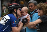 HM Place Sports: William Douglas Graham, Loudoun Now---Professional cyclist Lindsay Bayer gives her newborn a kiss as her mom looks on before starting the Armed Forces Cycling Classic bicycle race.
